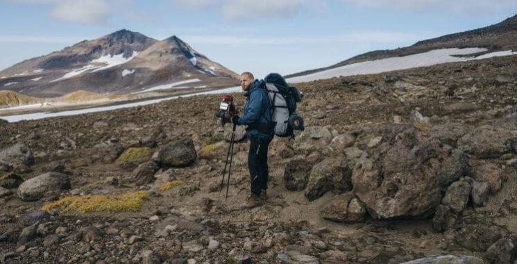 man hiking with camera bag
